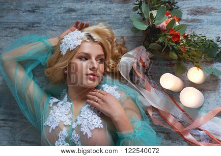 Charming young blond woman with curly hair holding fresh flowers bouquet with roses carnations and eucalyptus leaves. Bridal boudoir.