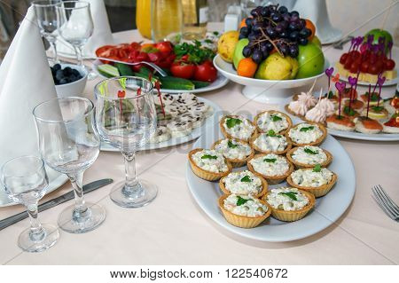 Sand tarts with filling, festive appetizer. Banquet table for guests. Served luxurious food table at the party. Interior of the Banquet hall in the restaurant, in white.