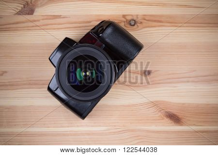Analog SLR camera with lens on wooden background