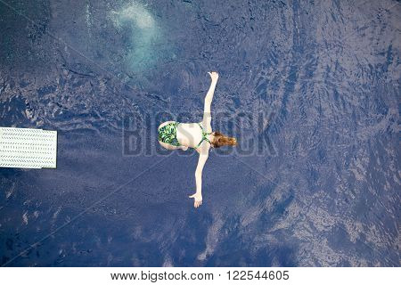 Springboard diver jumping into the swimming pool