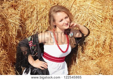 Beautiful young woman in a scarf and a white sundress near haystack in summer sunny day