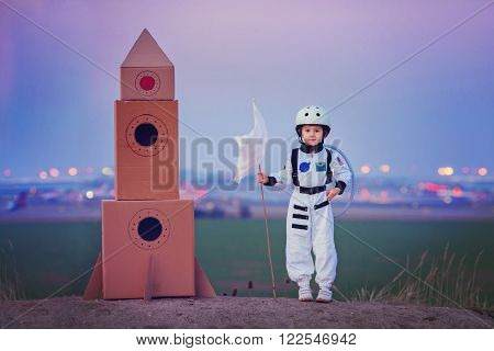 Adorable Little Boy, Dressed As Astronaut, Playing In The Park With Rocket And Flag