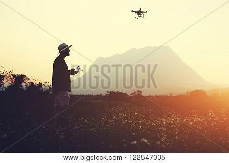 Silhouette of a man photographer is making picture with RC aerial camera while is standing in rural in evening. Male traveler is shooting video with flying multicopter during summer adventure abroad