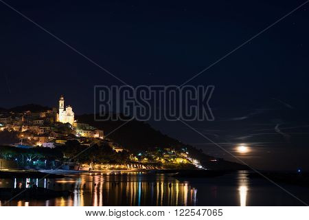 The historical town of Cervo glowing in the night under moonlight and starry sky on the coastline of Ligurian Riviera, famous travel destination in Italy.