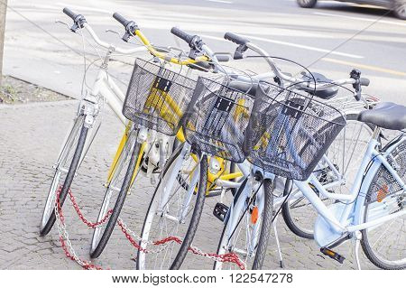 Four parked bicycles on the sidewalk chained together.