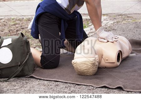 First aid training. Cardiopulmonary resuscitation (CPR) medical procedure - Demonstrating chest compression on CPR doll.