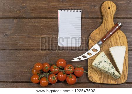 Cheese with white mold it and stainless steel cheese knife with wood handle are is lying on the board of olive wood. Cherry tomatoes and paper notebook are lying on a wooden board.