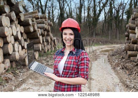 Female Forest Engineer Beside Logs