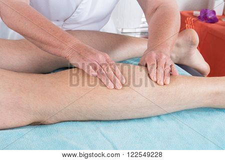 Extreme close up of osteopath applying pressure with thumb on male calf muscle.