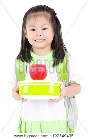 Asian primary school girl holding lunch box and apple. Healthy eating concept for schoolchild.