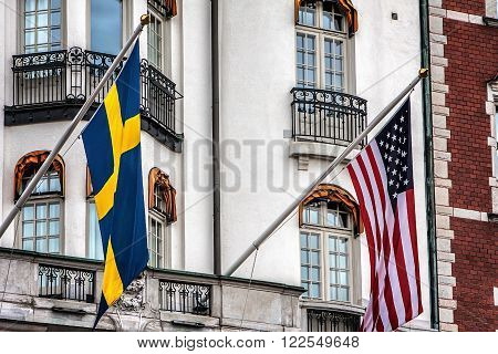 Building facade with Swedish and US flags.