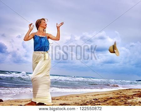 Summer girl sea.  Woman wearing sundress on coast near ocean with waves. Wind blew his hat.