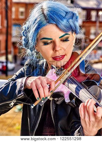 Portrait of music street performers girl violinist with blue hair playing  aganist sky with city outdoor.