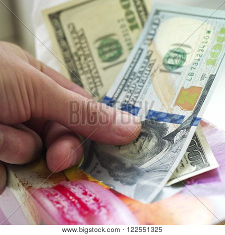 Male hand pulling out cash out of a tissue box macro shot finance concept