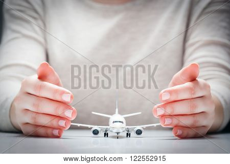 Airplane model surrounded by hands in gesture of protection. Concept of aircraft industry, airline safety, security and insurance.