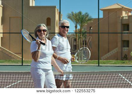 Portrait of an active senior couple on tennis court