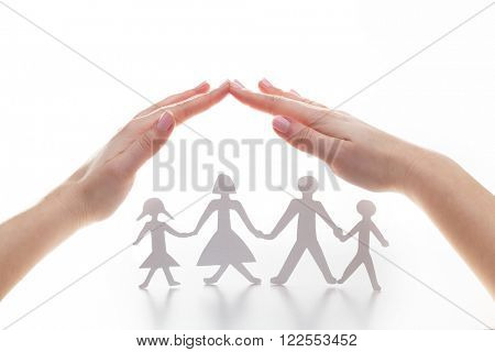 Paper family under hands in gesture of protection. Concept of insurance, family protection and support.