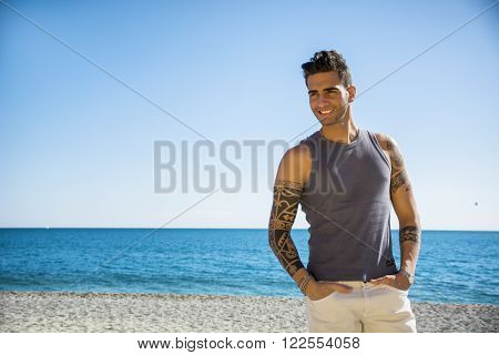 Half Body Shot of a Handsome Athletic Young Man in Trendy Attire, on a Beach in a Sunny Summer Day, Looking At Camera, Smiling against Blue Sky Background.