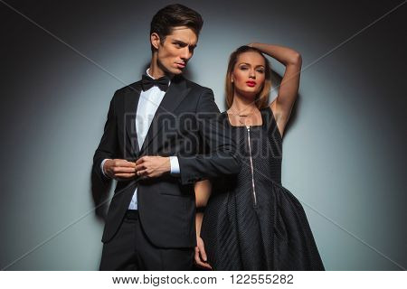 elegant couple in black posing in gray studio background. man stands in front fixing his jacket looking away while woman fixing her hair is looking at the camera.