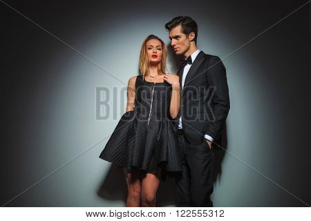 couple in black posing together in gray studio background. woman is fixing her dress while looking at the camera. man in business suit with hand in pocket is looking away