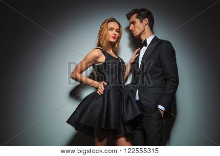 couple in black pose touching in gray studio background. woman with hand on waist touching man on chest while looking at the camera. man with hand in pocket looking at the woman.