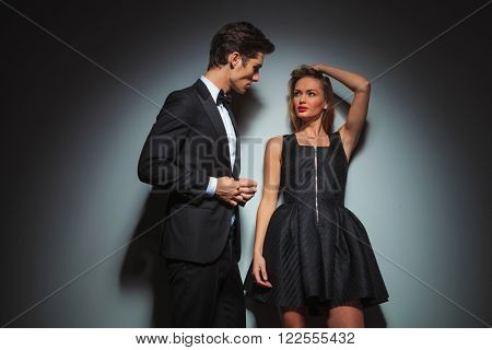 elegant couple in black posing in gray studio background. the man looks at the woman while fixing his jacket, while woman looks at the man fixing her hair and leaning on the wall.