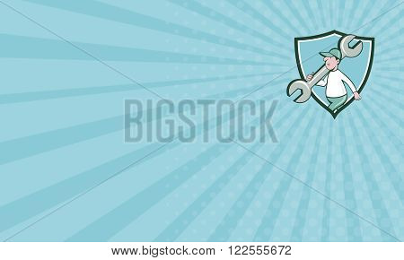Business card showing illustration of a mechanic wearing hat holding monkey wrench spanner on shoulder walking viewed from the side set inside shield crest on isolated background done in cartoon style.
