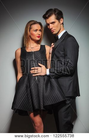 woman in black with legs crossed pulling man's jacket while looking away from the camera. businessman touching woman's dress while looking at the camera in gray studio background
