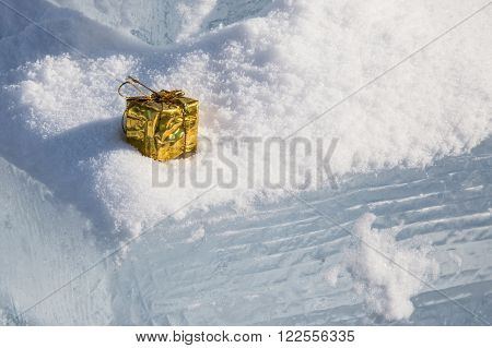 Little golden parcel stuck in snow on an ice block