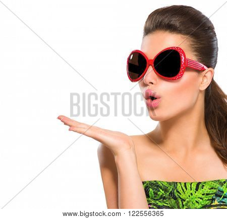 Beauty surprised fashion model girl wearing red sunglasses, with bright makeup showing empty copy space on open hand palm for text isolated on white background. Beautiful woman, summer fashion