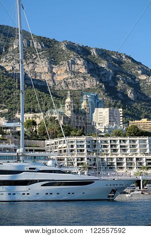 Monte Carlo, Monaco - September 20, 2015: sailboat yacht white modern beautiful at moorage in sea port on sunny summer day against mountains on cityscape background, vertical picture