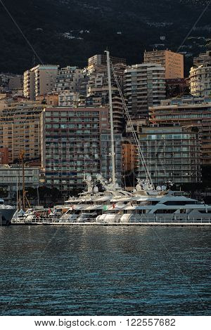 Monte Carlo, Monaco - September 20, 2015: yachts and sailboats modern vessels at moorage in sea port on sunny summer day against mountains on cityscape background, vertical picture