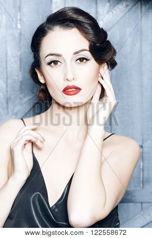 Portrait of attractive sensual glamour retro elegant young adult woman with classic hairstyle and red lips in silk night dress indoor on wooden background, vertical picture