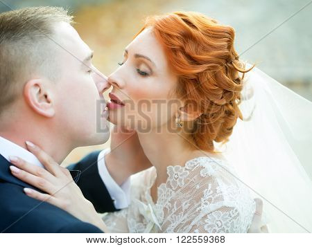 Wedding romantic couple of young red haired bride in white dress kissing with bridegroom outdoor on natural background, horizontal picture