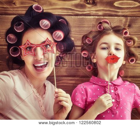 Funny family! Mother and her child daughter girl with a paper accessories. Beauty funny girl holding paper lips on stick. Beautiful young woman holding paper glasses on stick.
