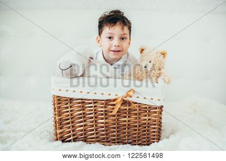 boy hid behind a basket with soft toys