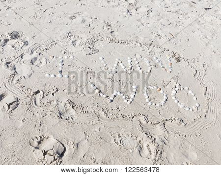 an inscription I wuv woo of small white shells and bright yellow sand fines with small stones and fragments of shells on the beach