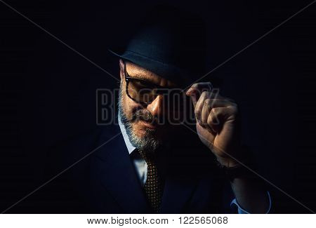 Older beard man respectfully holding a hat, wearing a classic male clothes with tie.