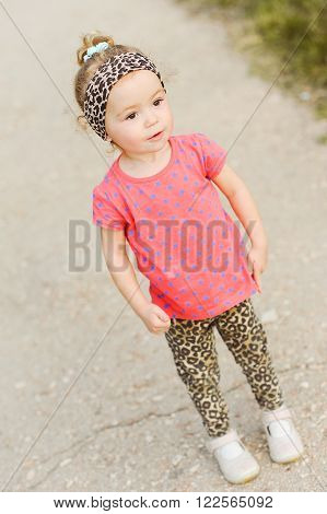 Stylish baby girl 3-4 year old walking in park. Childhood.