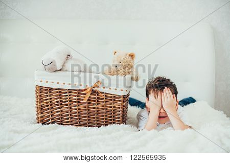 boy hid behind a basket with soft toys . hide-and-seek