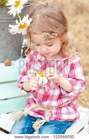 Cute baby girl 2-3 year old sitting on crate outdoors. Playful. Childhood. Summer time.