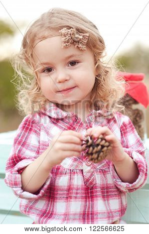Kid girl 3-4 year old playing with fir cones outdoors. Looking at camera. Childhood.