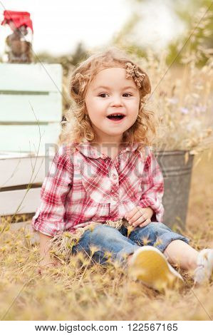 Laughing baby girl 2-3 year old sitting outdoors. Playful. Wearing stylish rustic clothes. Childhood.