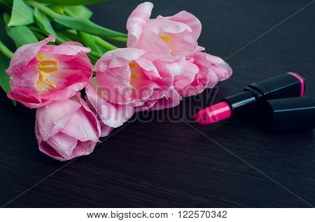Tulips with lipstick on dark wooden background with space for text. Spring flowers. March 8th mother's day valentine's day International Women's Day congratulate. Toned image.