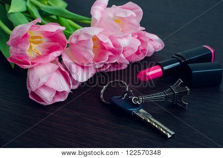 Tulips with lipstick on dark wooden background and key with Eiffel Tower. Spring flowers. March 8th mother's day valentine's day International Women's Day congratulate. Toned image.