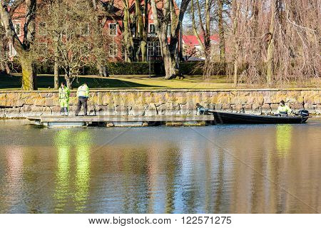 Kalmar Sweden - March 17 2016: Three persons are involved in transporting a floatable work platform or jetty through the canal using a small boat. Real people in everyday life.