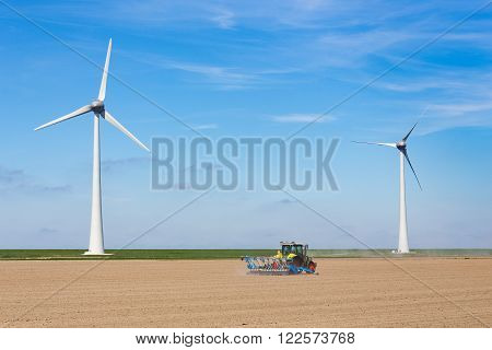 Farmer on tractor sowing in soil near dike and windmills