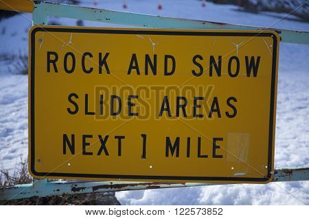 Yellow and black rock and snow slide areas next one mile sign
