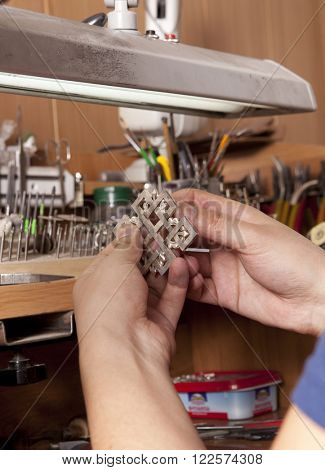 Jeweler crafting silver jewelry on his workbench
