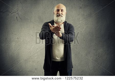 smiley senior man clapping and looking at camera over grey background
